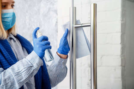 Woman Houseworker portrait in rubber blue gloves clean Door knob by cloth rag. Cleaning front door handle by antibacterial alcohol spray. New normal