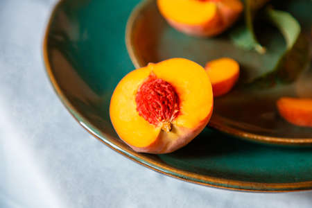 Peach in half with bone. Rustic minimalist food peach fruits with leaves on green plate on tablecloth. Harvest of Ripe juicy peaches. Still life Peaches fruit