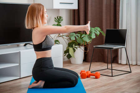 Sporty woman using dumbbells making fitness at home via laptop by remote video call online. Young woman losing weight by online remote gym workout.
