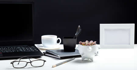 White table with laptop. Office homeworkspace for work or study in Office interior. Black laptop with blank display layout template on black background. Long web banner