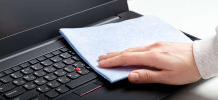 Female hands disinfecting laptop keyboard using wet disinfectant wipes. Woman cleaning keyboard. New Normal cleaning laptop work home surfaces. Long web banner