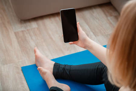 Mockup for app online fitness program, remote yoga class. Woman in sportswear holding Smartphone with empty screen for sport or music app during a workout break on mat at home against couch. Banco de Imagens