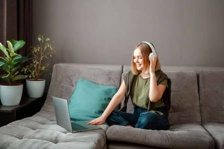 Happy young woman is sitting on sofa with laptop in headphones. Remote work, online study or online shopping. Rest at home interior of living room. Woman talking on video call at meeting from home