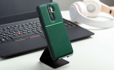 Smartphone on holder in protective case on Smartphone back near black laptop on Modern white work space. White table in home or office with phone laptop headphones. Long web banner
