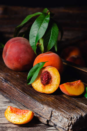 Juicy ripe peach on dark wooden rustic cutting board. Delicious farm peaches with leaves whole fruit in halves, peach with bone. Still life peach with in dark key. Vertical format