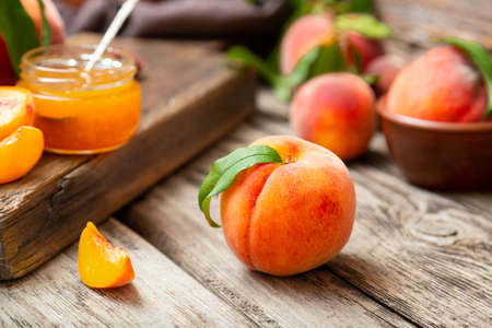 Whole peach fruit and wedges for making jam. Peach fruit with leaf. Ripe juicy orange peach fruit on wooden table. Peach harvest and jam on rustic kitchen closeup in dark mood Banco de Imagens