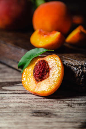 Peach with leaf on wooden table. Peaches in half. Ripe juicy peaches. Harvest of peaches for food or juice. Closeup Banco de Imagens