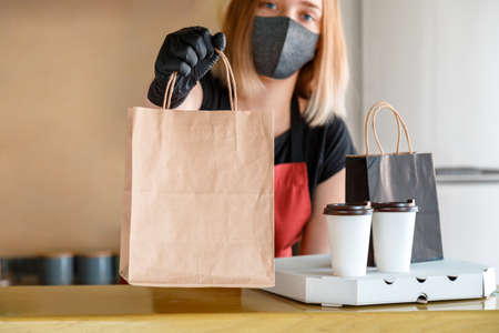 Food bag, pizza, drink package to go in takeaway restaurant. Kitchen worker issues online orders in gloves and mask. Takeaway food paper bag mock up. Contactless food delivery lockdown  .
