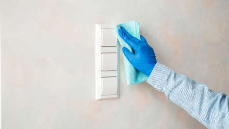 Light switch surfaces disinfection. Woman in rubber blue glove clean light switch with cloth on wall by wet rag. New normal virus in sanitize. Housework clean service. Long web banner Zdjęcie Seryjne