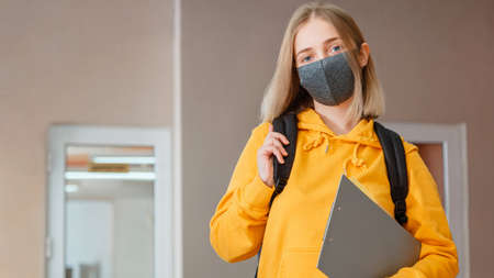 Schoolgirl in mask with backpack. Young woman student in protective medical mask. Portrait of blonde female student Girl at university interior during virus lockdow. Long web banner.