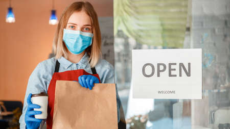 Woman waiter in protective medical mask and gloves giving takeaway orders. Food delivery Long web banner Reopening Door Sign Open welcome after lockdown on front door entrance.Reopen new normal