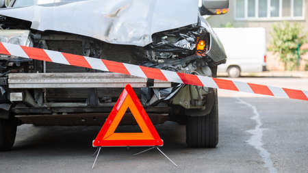 Red emergency stop triangle sign and Red warning police tape afore. Destroyed car in car crash traffic accident on city road. Smashed broken car in accident. Smashed broken headlight. Long web banner.