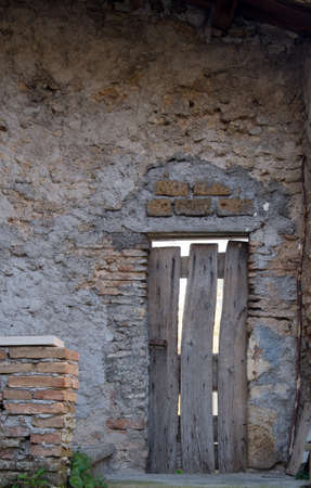 Ancient wooden door in old stone wall,front view