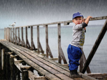 rainwear: Waiting child by the sea in heavy storm                             Stock Photo