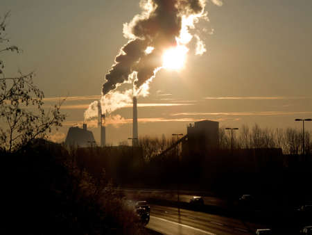 smoke coming from a factory in the early morning. The chimney casts a special shadow on the smoke Stock Photo - 6343708