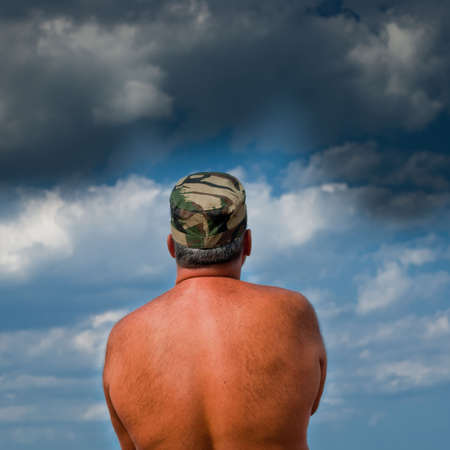 Shirtless army man waiting for the storm to come. photo
