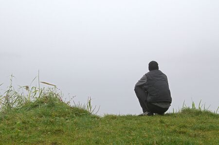 Autumn early morning. Riverside. Thick fog. A young man is sitting on the green grass, squatting. He looks at the river, at the fog. Man thinks, reflects, rests. Autumn.