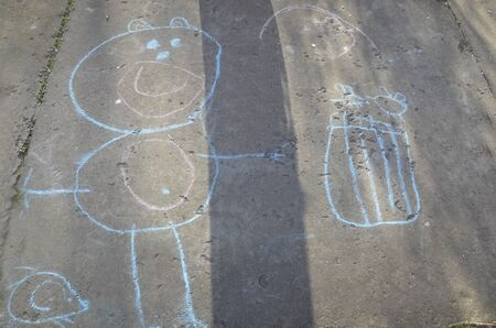 Children's drawing on the asphalt. The child drew a funny and funny image, a picture. Humor, joke.