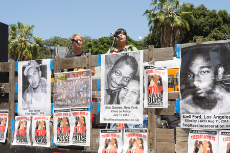 decades: Los Angeles, CA, USA - April 14, 2015:: Woman speaking about people murdered by police during Stop Murder by Police. Protest against the brutalization and murdering of black and latino people by police for decades without consequence.