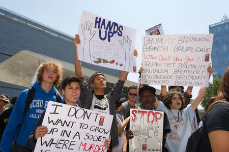anarchist: Los Angeles, CA, USA - April 14, 2015:  Group of people holding signs and blowing whistles during Stop Murder by Police. Protest against the brutalization and murdering of black and latino people by police for decades without consequence. Editorial