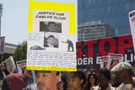 murdering: Los Angeles, CA, USA - April 14, 2015:  Latino man holding sign for justice during Stop Murder by Police. Protest against the brutalization and murdering of black and latino people by police for decades without consequence.