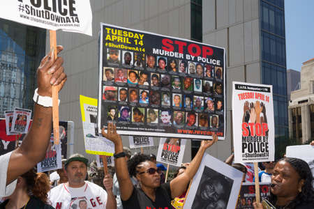 decades: Los Angeles, CA, USA - April 14, 2015:  Woman showing pictures of people murdered by police during Stop Murder by Police. Protest against the brutalization and murdering of black and latino people by police for decades without consequence.