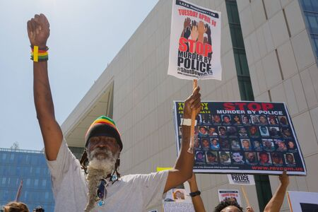 decades: Los Angeles, CA, USA - April 14, 2015:  Man raising hand for justice during Stop Murder by Police. Protest against the brutalization and murdering of black and latino people by police for decades without consequence. Editorial