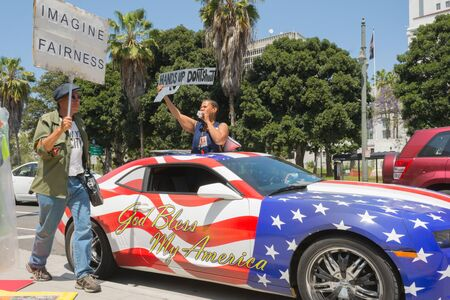decades: Los Angeles, CA, USA - April 14, 2015:  People holding sign next to a car painted in american flag colors during Stop Murder by Police. Protest against the brutalization and murdering of black and latino people by police for decades without consequence.