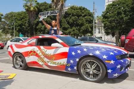 decades: Los Angeles, CA, USA - April 14, 2015:  Woman holding sign next to a car painted in american flag colors during Stop Murder by Police. Protest against the brutalization and murdering of black and latino people by police for decades without consequence.