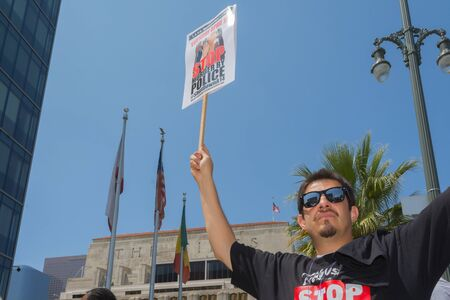 decades: Los Angeles, CA, USA - April 14, 2015: Man wearing stop murder by police shirt and holding sign  during Stop Murder by Police. Protest against the brutalization and murdering of black and latino people by police for decades without consequence.