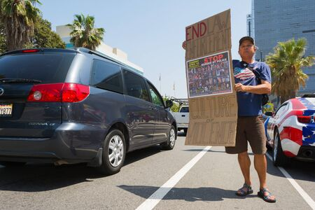 decades: Los Angeles, CA, USA - April 14, 2015:  Man holding sign during Stop Murder by Police. Protest against the brutalization and murdering of black and latino people by police for decades without consequence.