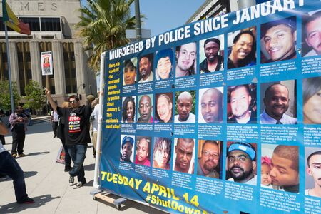 murdering: Los Angeles, CA, USA - April 14, 2015:  Man next to banner  during Stop Murder by Police. Protest against the brutalization and murdering of black and latino people by police for decades without consequence. Editorial