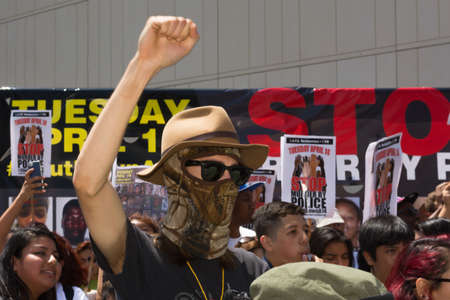 consequence: Los Angeles, CA, USA - April 14, 2015:  Man wearing face mask raising hand for justice during Stop Murder by Police. Protest against the brutalization and murdering of black and latino people by police for decades without consequence. Editorial