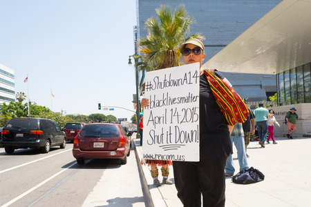 decades: Los Angeles, CA, USA - April 14, 2015:  Woman showing sign to passersby during Stop Murder by Police. Protest against the brutalization and murdering of black and latino people by police for decades without consequence.