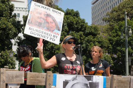 consequence: Los Angeles, CA, USA - April 14, 2015: Woman speaking about innocent man murdered by police during Stop Murder by Police. Protest against the brutalization and murdering of black and latino people by police for decades without consequence.