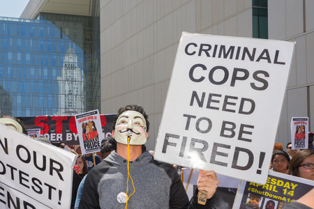 decades: Los Angeles, CA, USA - April 14, 2015:  Man wearing mask holding a sign during Stop Murder by Police. Protest against the brutalization and murdering of black and latino people by police for decades without consequence.