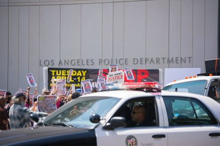 decades: Los Angeles, CA, USA - April 14, 2015: Police observing people in front of Los Angeles Police Department during Stop Murder by Police. Protest against the brutalization and murdering of black and latino people by police for decades without consequence.