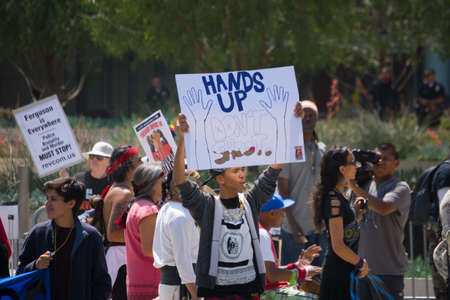 consequence: Los Angeles, CA, USA - April 14, 2015:  Boy with raised sign blowing whistle during Stop Murder by Police. Protest against the brutalization and murdering of black and latino people by police for decades without consequence.