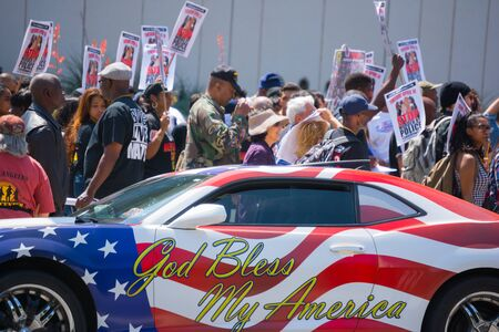 murdering: Los Angeles, CA, USA - April 14, 2015:  Car painted with american flag colors in front of protestors  during Stop Murder by Police. Protest against the brutalization and murdering of black and latino people by police for decades without consequence.