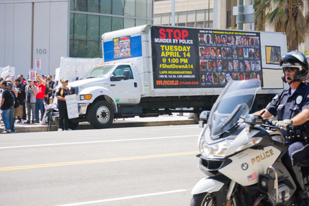 decades: Los Angeles, CA, USA - April 14, 2015:  Truck with banner parked in front of police department during Stop Murder by Police. Protest against the brutalization and murdering of black and latino people by police for decades without consequence.