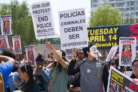 consequence: Los Angeles, CA, USA - April 14, 2015:  Man wearing mask holding a sign and blowing a whistle during Stop Murder by Police. Protest against the brutalization and murdering of black and latino people by police for decades without consequence. Editorial