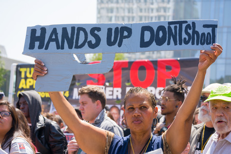 decades: Los Angeles, CA, USA - April 14, 2015:  Woman raising a sign in the form of a gun during Stop Murder by Police. Protest against the brutalization and murdering of black and latino people by police for decades without consequence. Editorial
