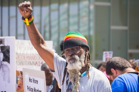 murdering: Los Angeles, CA, USA - April 14, 2015:  Man with beard raising hand for justice during Stop Murder by Police. Protest against the brutalization and murdering of black and latino people by police for decades without consequence.