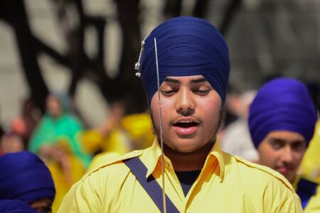 recite: Los Angeles, CA, USA - April 5, 2015: Devotee Sikh with blue turban recite prayer at the Anniversary of Baisakhi celebration.