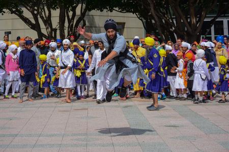sikh: Los Angeles, CA, USA - April 5, 2015: Devotee Sikh man dancing at the Anniversary of Baisakhi celebration.