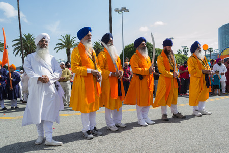 devotee: Los Angeles, CA, USA- April 5, 2015: Devotee Sikhs with blue turbans holding swords at the Anniversary of Baisakhi celebration. Editorial