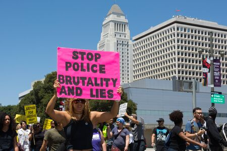 in custody: Los Angeles CA USA  May 02 2015: Woman raising a sign in march against the death of Freddie Gray a man of Baltimore who was seriously injured in police custody.