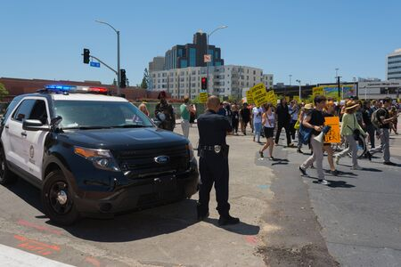 resulted: Los Angeles CA USA  May 02 2015: Police watching Protestants during march against the death of Freddie Gray a man of Baltimore who was seriously injured in police custody.