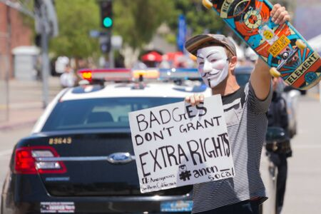 resulted: Los Angeles CA USA  May 02 2015: Masked man holding poster during march against the death of Freddie Gray a man of Baltimore who was seriously injured in police custody.