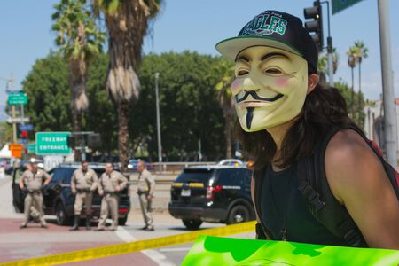in custody: Los Angeles CA USA  May 02 2015: Anonymous with mascara with police in the background during march against the death of Freddie Gray a man of Baltimore who was seriously injured in police custody.